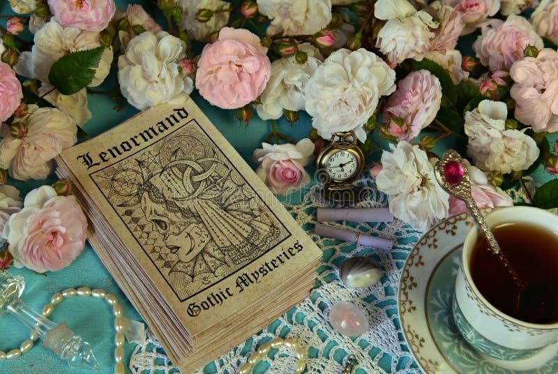 Stilleben med den Lenormand tarokkort, rosor och koppen arkivfoton