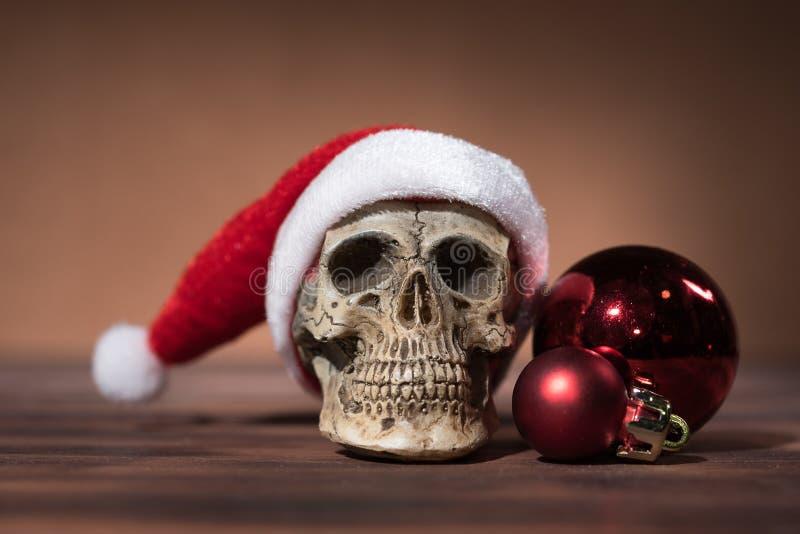 Stilleben med den Santa Claus skallen och röda julbollar royaltyfri foto