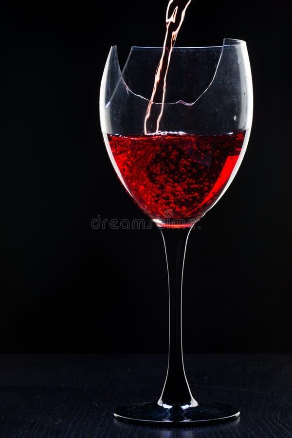 Stilleben med det brutna exponeringsglaset för vin på svart royaltyfri fotografi