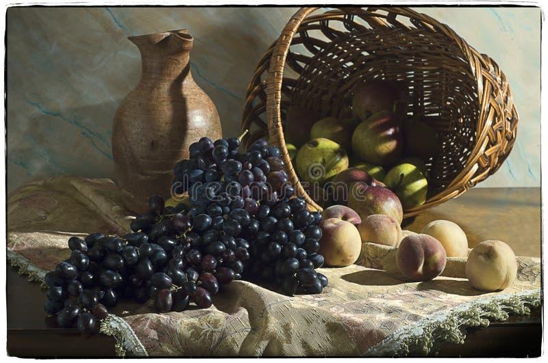 Stilleben med druvor, persikor och päron i en korg royaltyfri bild