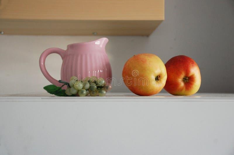Stilleben med en tillbringare och äpplen och druva royaltyfri fotografi