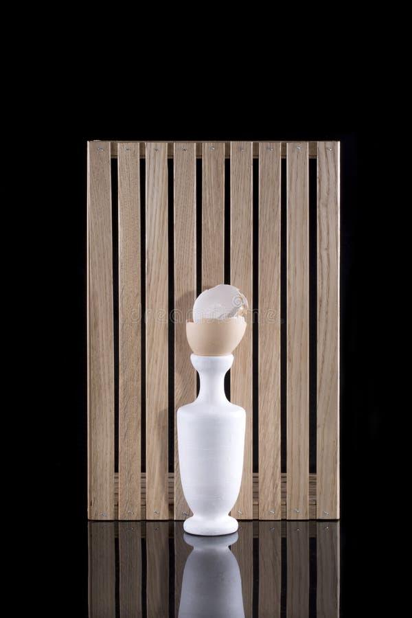 Stilleben med en vit vas och ett brutet fegt äggskal royaltyfria bilder