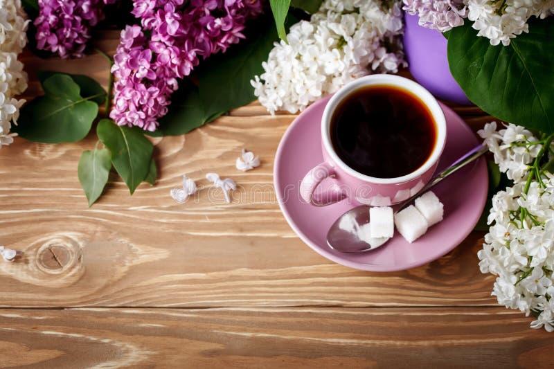 Stilleben med filialer av lilan och en kopp kaffe på en trätabell royaltyfria foton