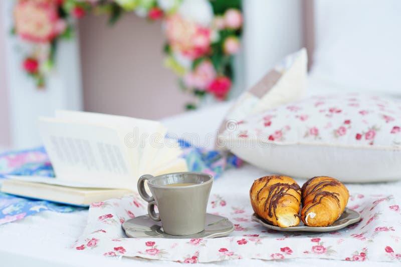 Stilleben med frukosten och boken i säng royaltyfri foto