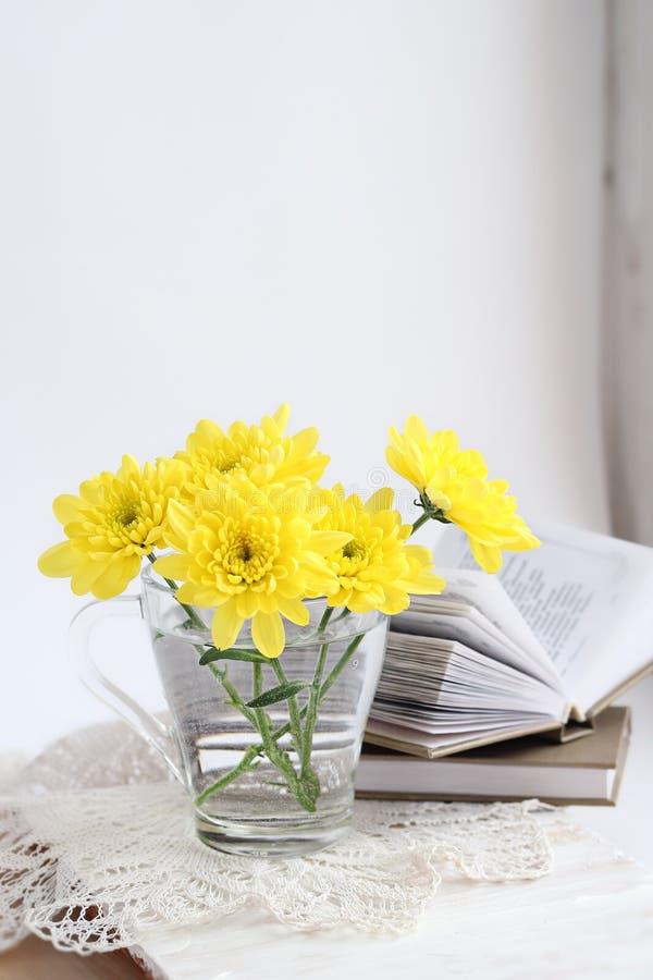 Stilleben med gula chrysathemums och böcker royaltyfria foton