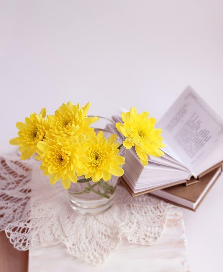 Stilleben med gula chrysathemums och böcker arkivfoto