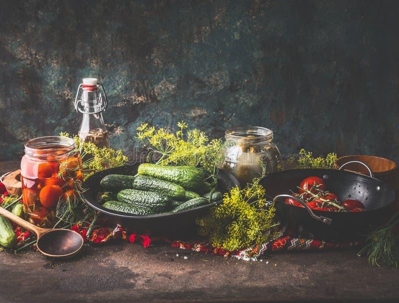 Stilleben med gurkan och tomater som gravar, på burk och bevarar ingredienser på den lantliga tabellen på mörk väggbakgrund royaltyfri bild