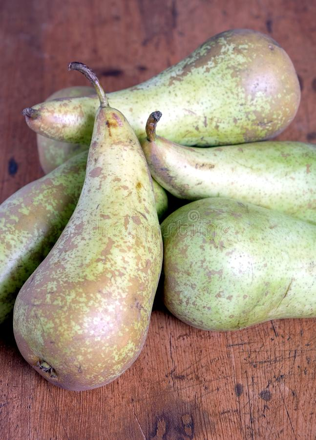 Stilleben med högen av långa mogna gröna päron på främre sikt för trätabell arkivfoton