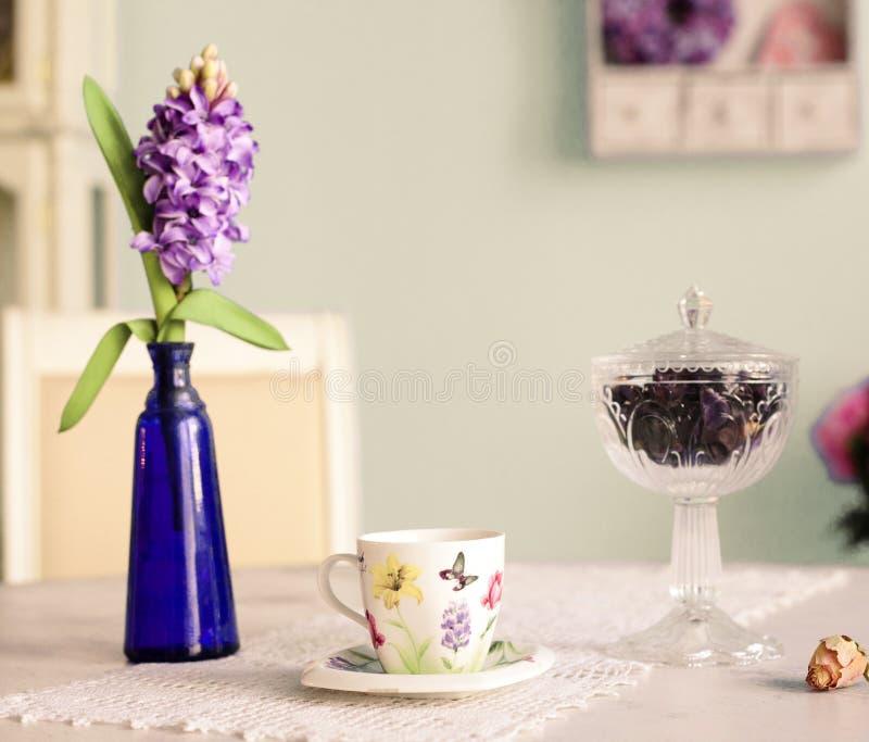 Stilleben med koppen för te för vashyacintblommor steg och wal blått royaltyfri foto