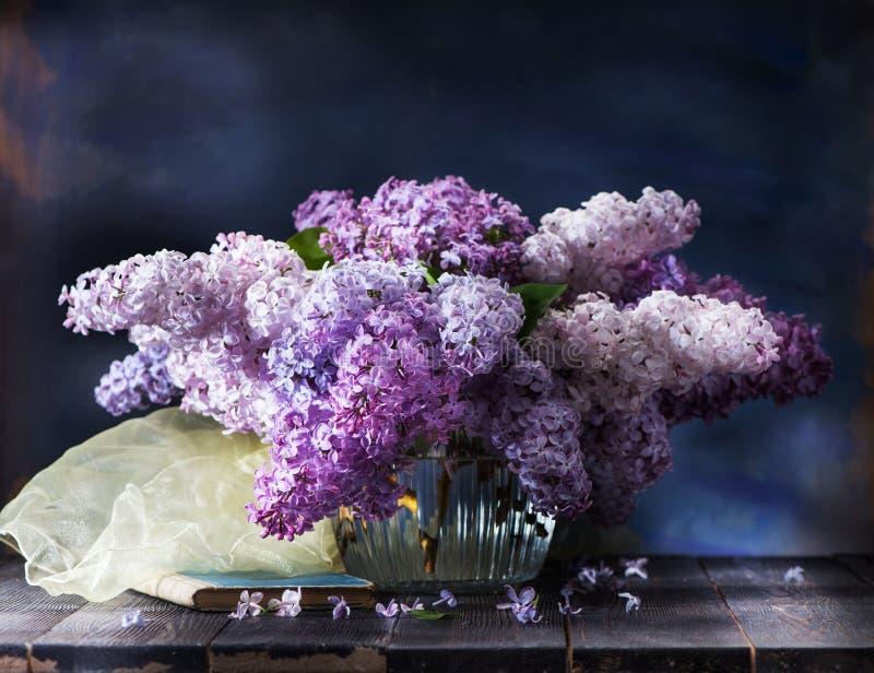 Stilleben med lilan blommar i en vas, en gammal bok och en silkehalsduk royaltyfria foton