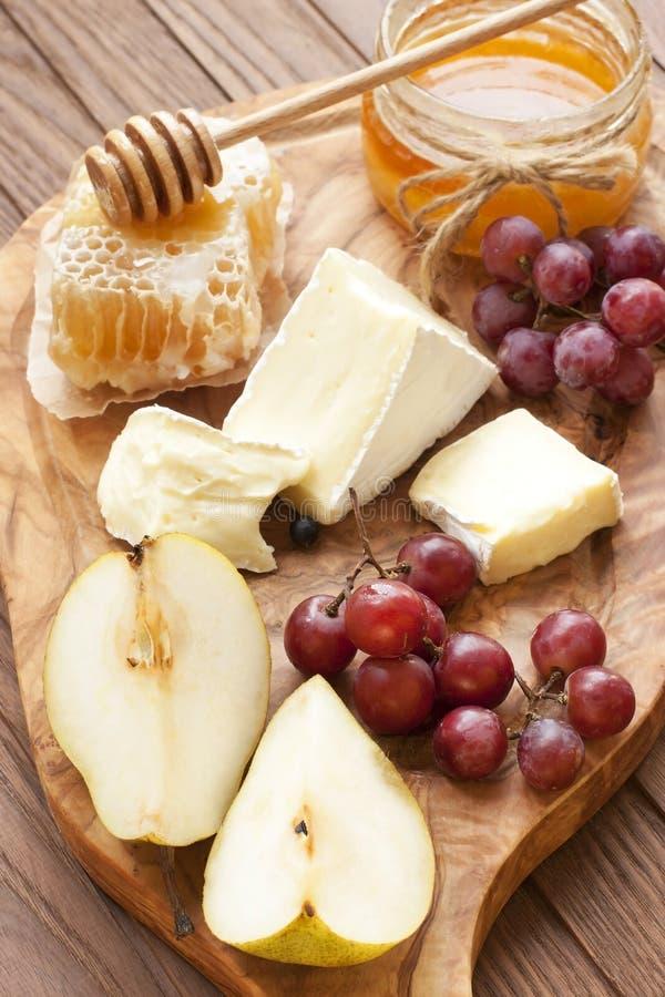 Stilleben med ost, druvan och honung royaltyfria bilder