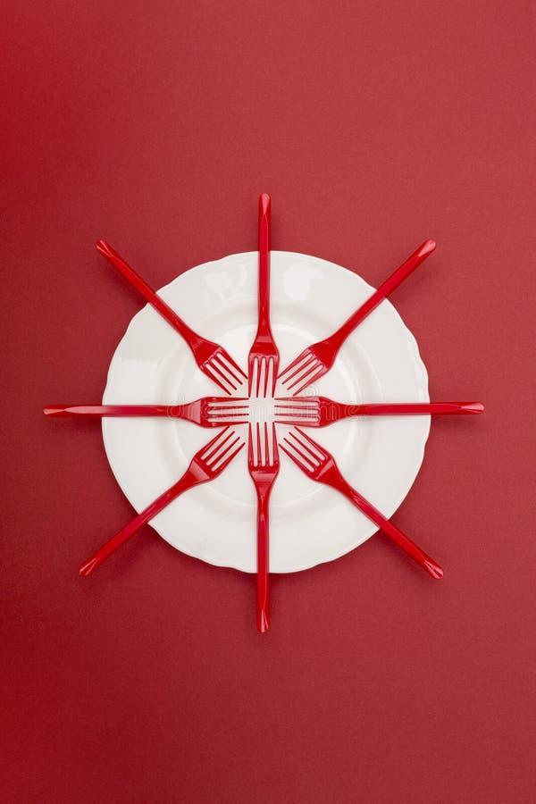 Stilleben med plast-gafflar och en platta på en röd bakgrund royaltyfri foto