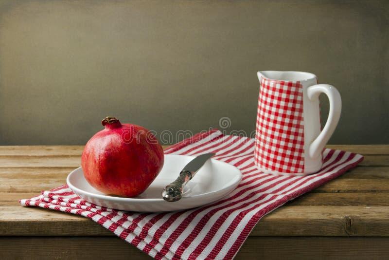 Stilleben med pomegranaten och tillbringaren arkivfoto