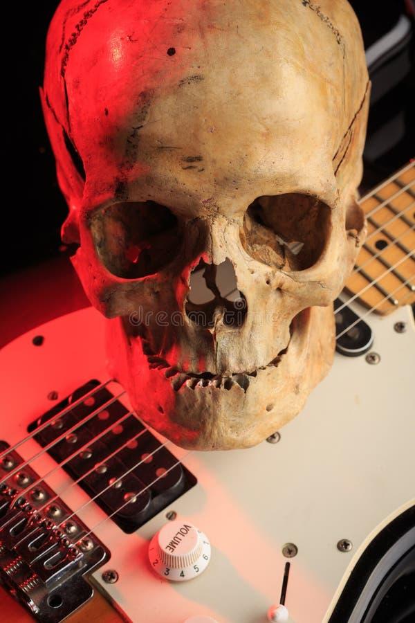 Stilleben med skallen och den elektriska gitarren arkivfoton