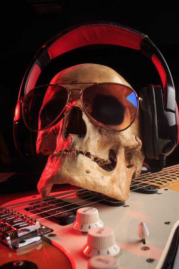 Stilleben med skallen och den elektriska gitarren arkivfoto