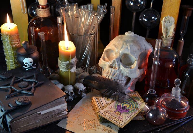 Stilleben med skallen, tarokkort och magiflaskor arkivbilder