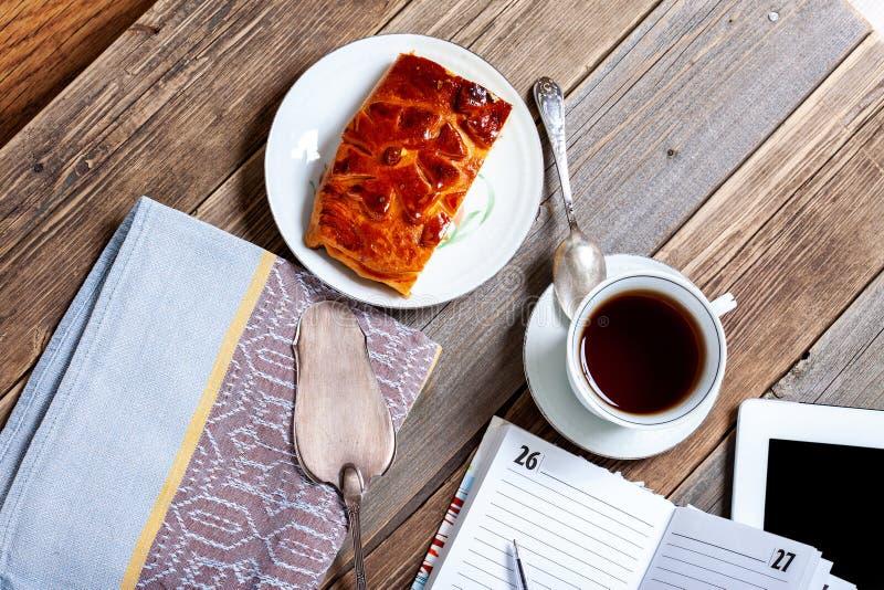 Stilleben med te, kakan, minnestavlan och plan arkivbild