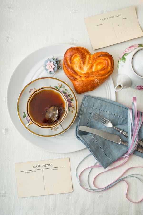 Stilleben med te- och älsklingbullen på den vita tabelllodlinjen royaltyfri fotografi