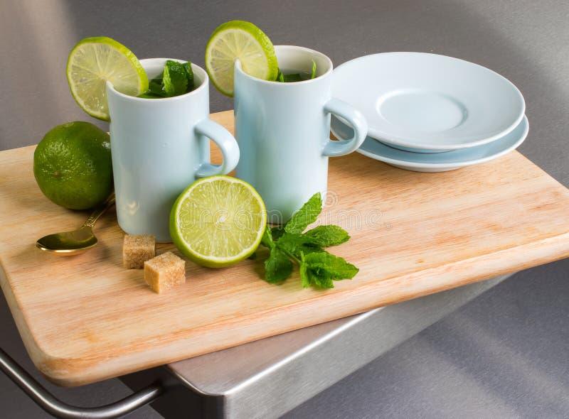 Stilleben med te och limefrukt för ny mintkaramell royaltyfria bilder