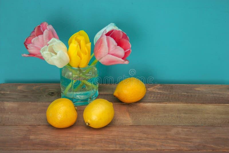 Stilleben med tulpan och citroner arkivbild