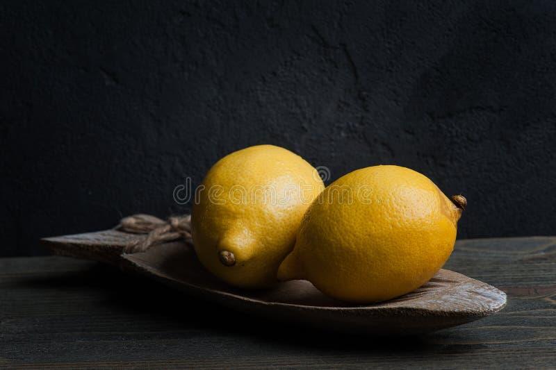 Stilleben med två citroner Mörkret utformar royaltyfria bilder
