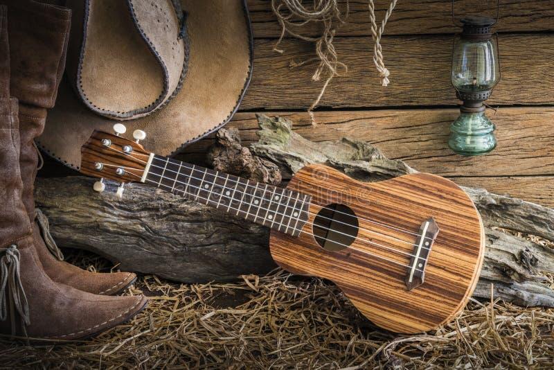 Stilleben med ukulelet på cowboyhatten och traditionellt läder bo arkivfoton