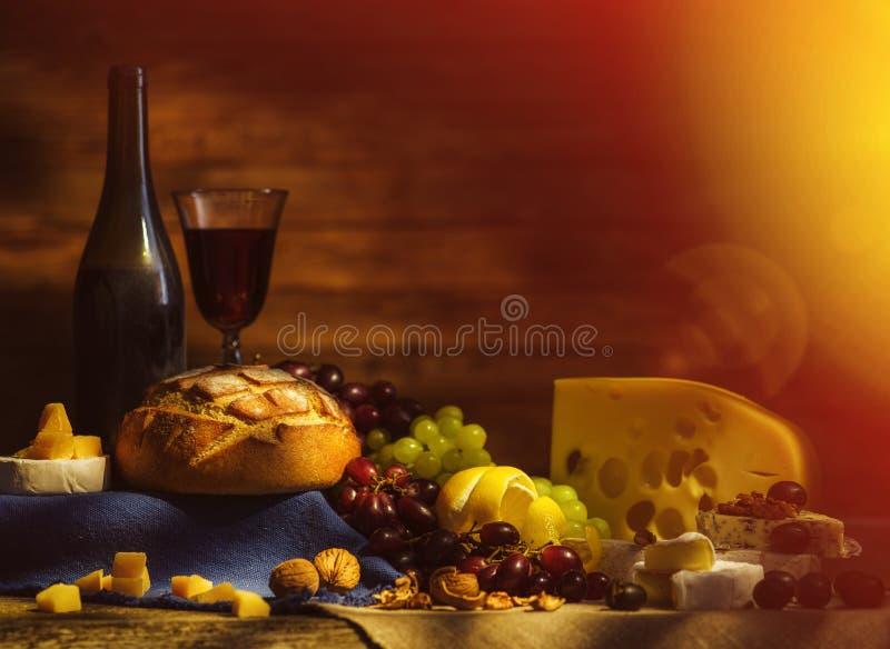 Stilleben med vin, druvor, bröd och olika slag av ost royaltyfria bilder