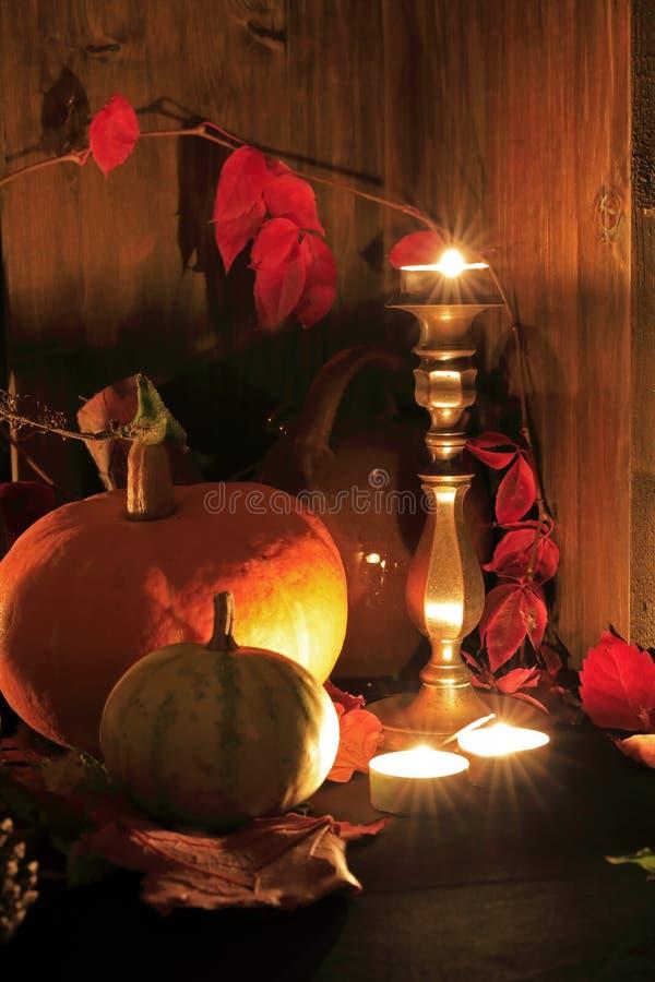 Stilleben på allhelgonaaftonen med pumpastearinljus och röda sidor royaltyfri foto