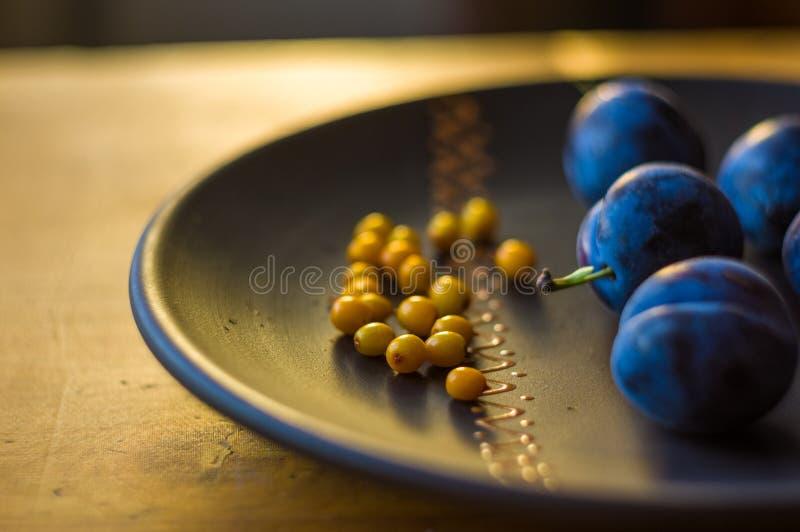 stilleben - saftiga blåa plommoner och havsbuckthornbär i en keramisk platta på en träbakgrund royaltyfri fotografi