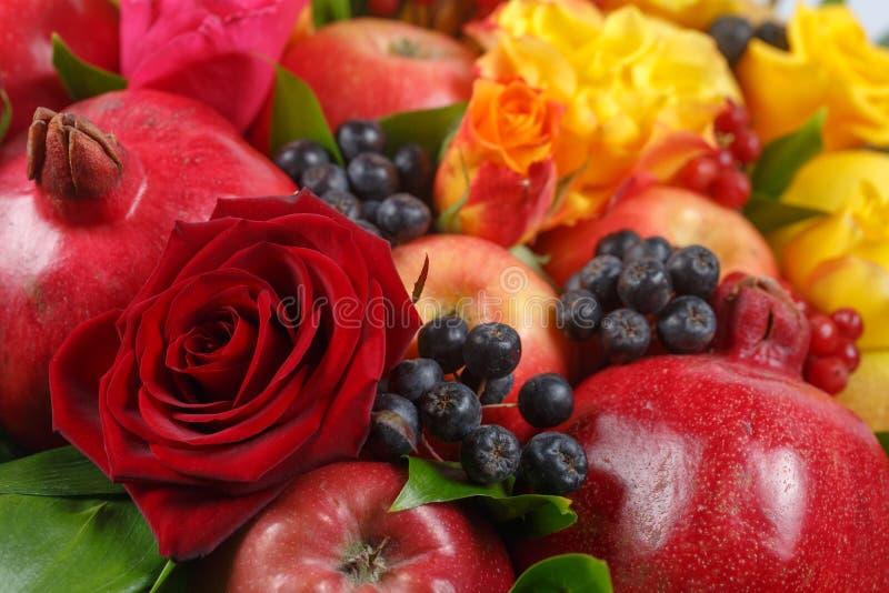 Stilleben som består av granatäpplen, äpplen, den svarta rönnen, den röda viburnumen, päron, citroner och blommor av röda och gul royaltyfri fotografi