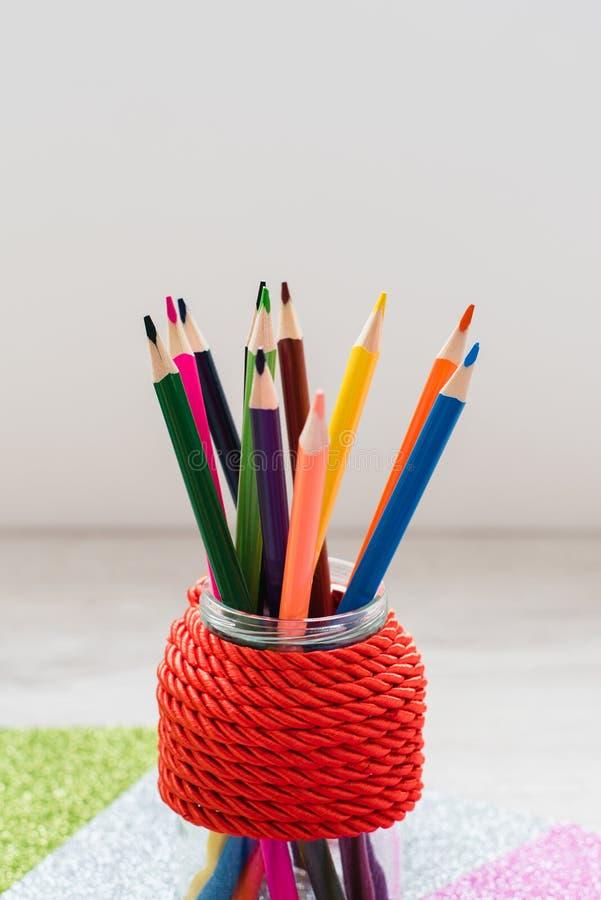 Stilleben som en gräsplan rånar fyllt med färgrika blyertspennor mot en vägg för röd tegelsten royaltyfria bilder