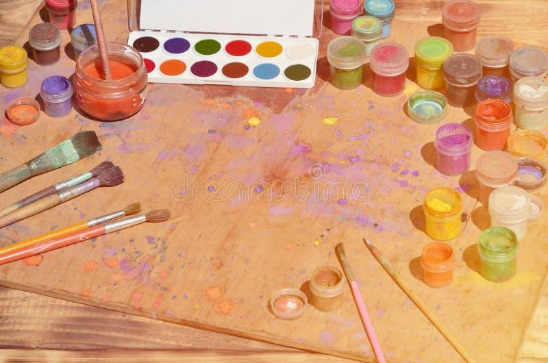 Stilleben som visar ett intresse i vattenfärgmålning och konst Många borstar, krus med vattenfärgen målar och använde gouachelögn royaltyfri fotografi