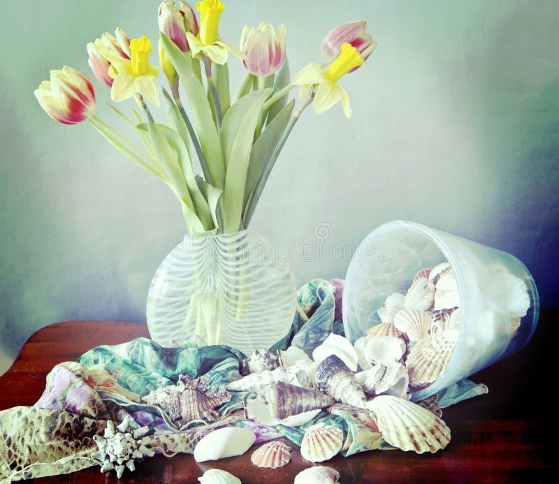 Stilleben, vårblommor, skal och siden- scarves royaltyfri fotografi