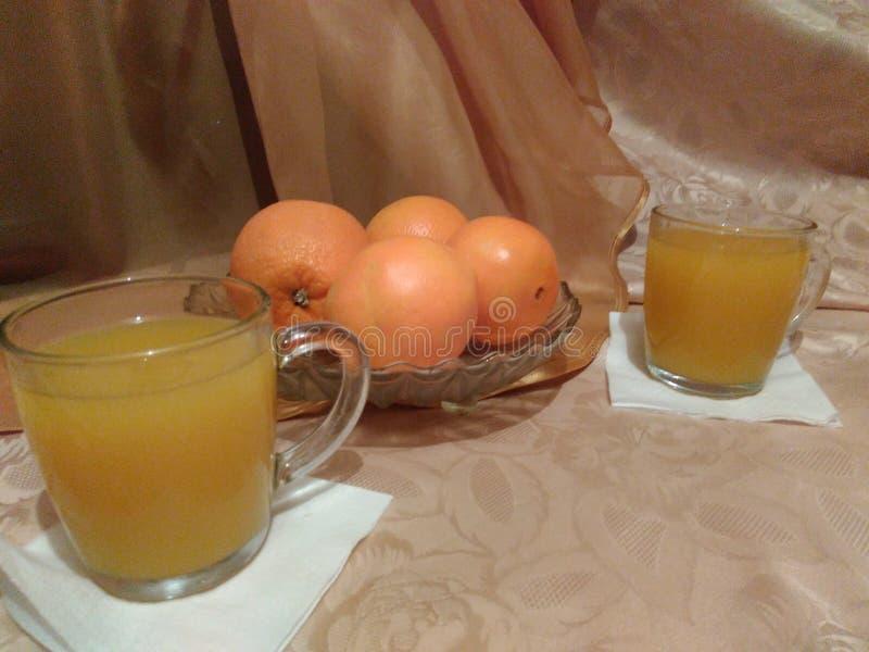 Stillebenapelsiner i en exponeringsglasvas och en ny orange fruktsaft arkivfoto