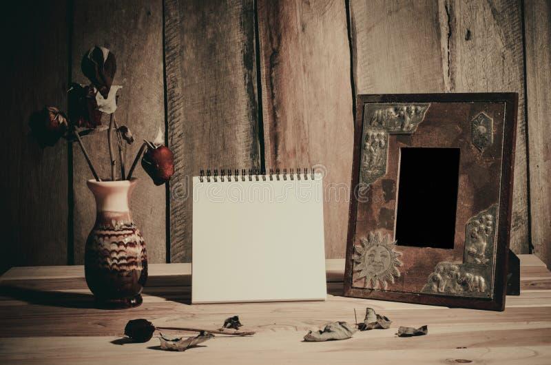 Stillebenbildramar, vaser, torkade vanliga minnen för rosa anteckningsbokbegrepp royaltyfria foton