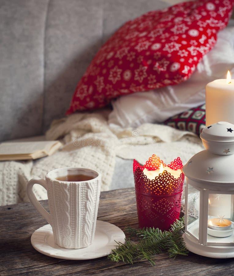 Stillebeninredetaljer, kopp te, stearinljus nära soffan royaltyfri foto