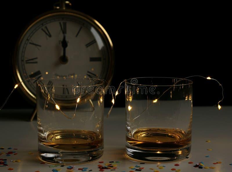Stillebensammansättning för nytt år med kulöra konfettier, drinkexponeringsglas och klockaplattan Partigarnering, berömbegrepp si royaltyfri fotografi