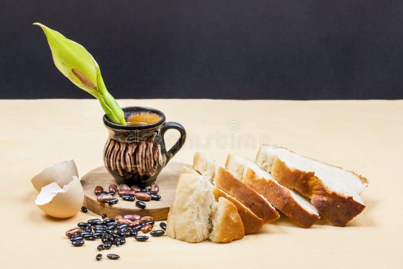 Stillebensammansättning med träkökskärbrädan, bönor, äggskalet, bröd och den keramiska krukan med munkhätta blommar royaltyfri foto