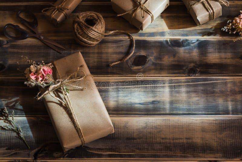 Stillebenskott av den härliga lilla handgjorda packen för DIY-gåvaask med blommor och det dekorativa repet på träbakgrund Tappnin arkivbild