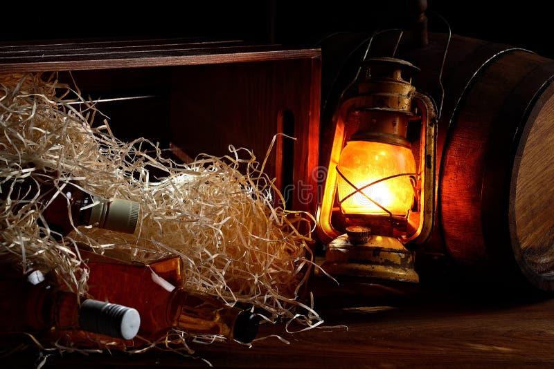 Stilleven 1 bourning olie ouderwetse lamp, houten container met houten spaanders en houten vaten Whiskyflessen stock afbeelding