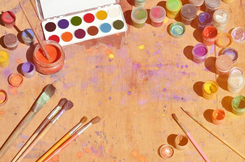 Stilleven, die een rente in waterverf het schilderen en art. tonen Heel wat borstels, kruiken met waterverfverf en gebruikte goua stock foto
