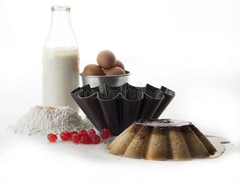 Stilleven die uit een eivla, een krullende vorm, een fles melk, een kom met eieren, bloem en eierdooier bestaan stock fotografie
