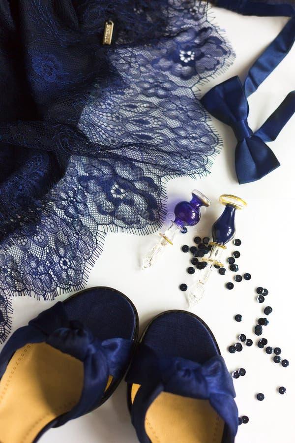Stilleven in donkerblauwe kleur: fragment van blauwe kantkleding, blauwe satijnschoenen, haastige vlinder stock fotografie