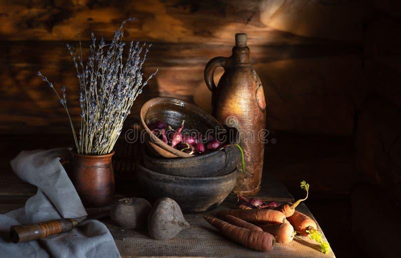 Stilleven in een dorpshut oude ceramische schotels en groenten op de lijst in de ochtendzon stock foto's