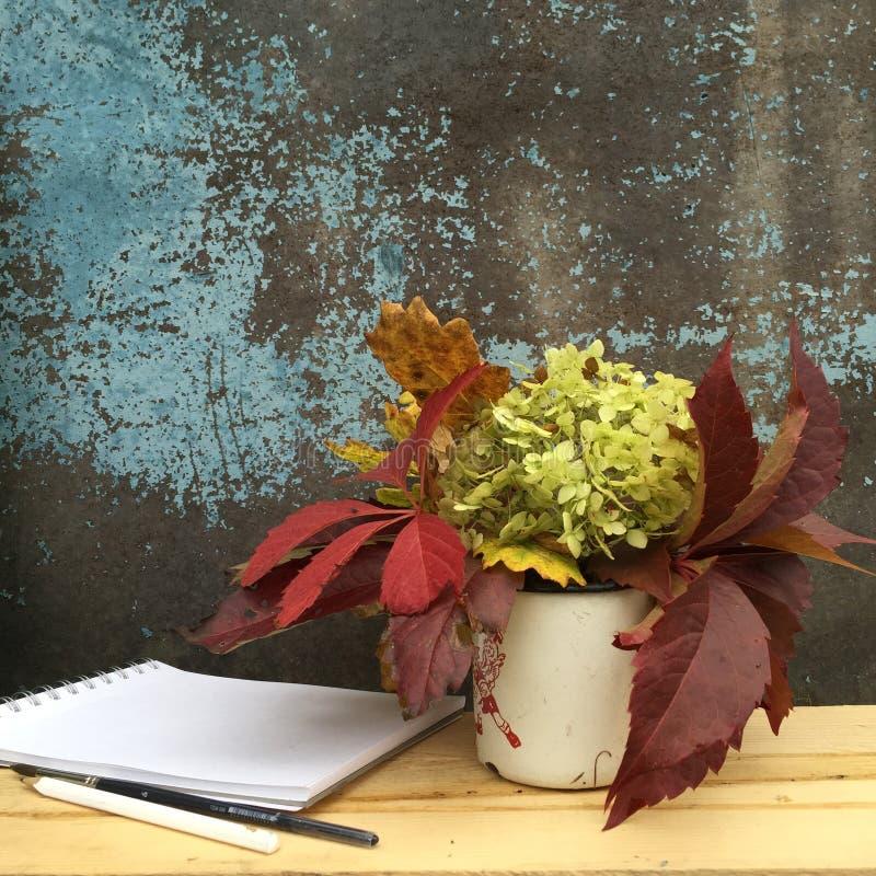 Stilleven: klein boeket van hydrangea hortensia's en druivenbladeren in een oude ijzerkop en toebehoren voor tekening royalty-vrije stock foto's