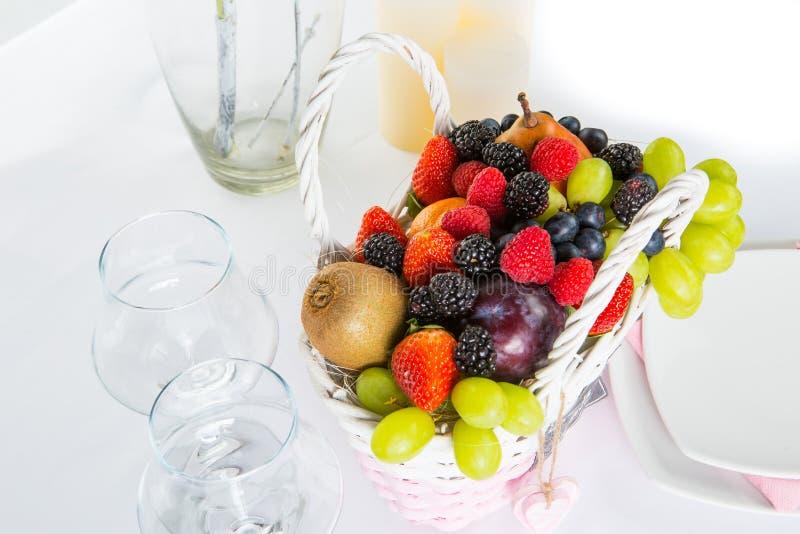Stilleven: mand met vruchten en bessen, koffiekoppen en kaarsen stock foto's