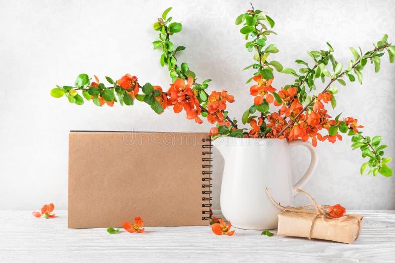 Stilleven met de mooie lente oranje bloemen, kop thee en leeg document notitieboekje op witte lijst Spot omhoog royalty-vrije stock foto's