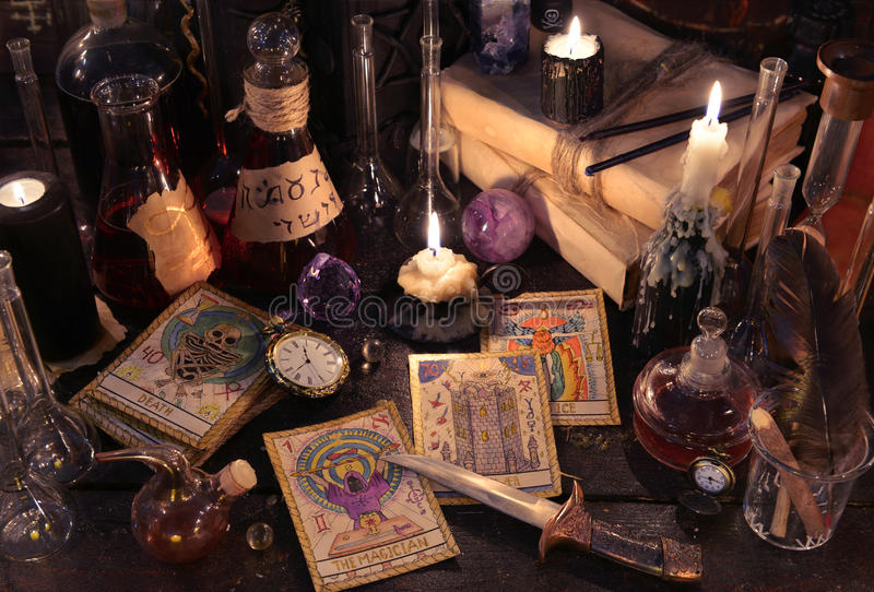 Stilleven met de tarotkaarten, mes, boeken en kaarsen op heksenlijst stock afbeelding