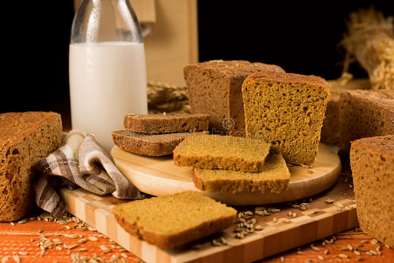 Stilleven met een glaskruik melk, roggebrood, korenaren stock fotografie