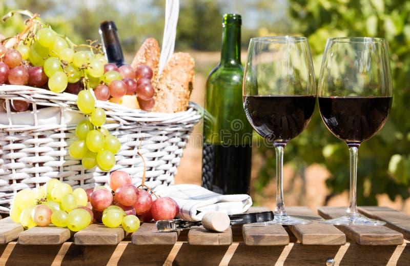 Stilleven met glas van rode wijndruiven en picknickmand op lijst stock fotografie
